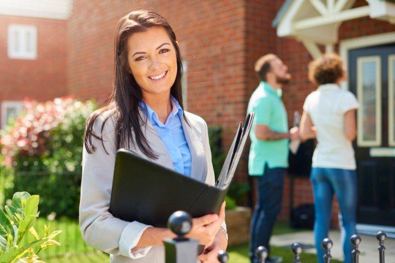 pośrednik nieruchomości natle domu zpotencjalnymi kupcami